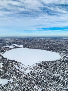 Snow arts; Aerial view of snow covered city in winter. Snoe delineates city streets, parks and roads.