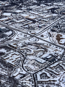 Snow arts; aerial view of city covered with snow in winter. Comples traffic interchange, city streets and roads and buildings delineated by snow.