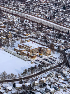 Snow arts; aerial photo of city covered with snow in winter. A municipal building with terraced seats possibly recreational center. City roads and streets outlined by snow.