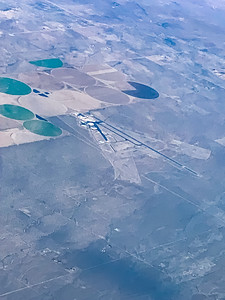 Snow arts; aerial view of landing air strip in a desert agricultural community with some snow cover