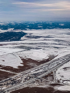 Snow arts; snow covered city suburb with complex interchange in the foreground