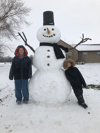 Heath Westendorf and Reese O'Dell stand with a 7-foot snowman at their home in Windsor.<br /> Submitted by Katie O'Dell
