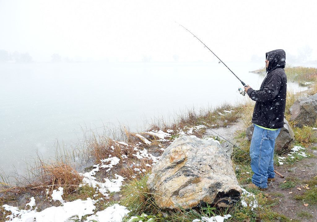 ". Lons Marquez fishes for trout and caftfish at Lake McClellan Monday morning. Marquez said he wasn\'t going to let the snow stop him from fishing on his day off of work. ""It gets me away from the house,\"" he said. Lewis Geyer/Staff Photographer Oct. 09, 62017"