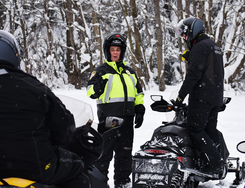 HOLLY PELCZYNSKI - BENNINGTON BANNER Kyle Case, of Colebrook CT stops for a check of insurance and registration by Bennington Police Chief, Pau Doucette on Friday morning in Woodford VT.  Doucette and others on the Snow Mobile Task force has increased patrols in Woodford after in influx of 3-4 feet of snow dropped in Woodford after the recent Nor'Easter.