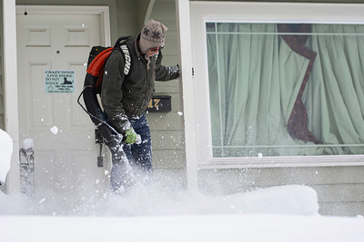 Robert Little of Port Angeles uses a leaf blower to clear snow on Wednesday Jan. 15, 2020. (Jesse Major)