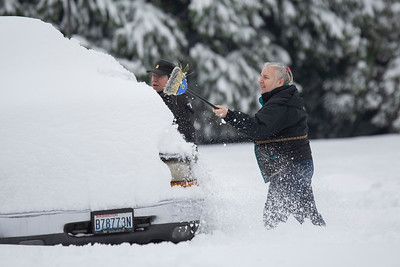 Susan McCormick of Port Angeles uses a broom to clear a foot of snow from a car on Wednesday, Jan. 15, 2020. (Jesse Major)