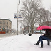 Fitchburg resident Melissa (no last name given) tries to stay dry as she waits for the bus on Monument Square in Leominster. SENTINEL & ENTERPRISE/JOHN LOVE