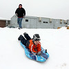 Tom Indge watches as his son Charlie, 6 both from Lunenburg, slides down the hill next to The Frances Drake Elementary School during the storm on Tuesday February 7, 2017. In the background a backhoe plow the parking lot of the school. SENTINEL & ENTERPRISE/JOHN LOVE