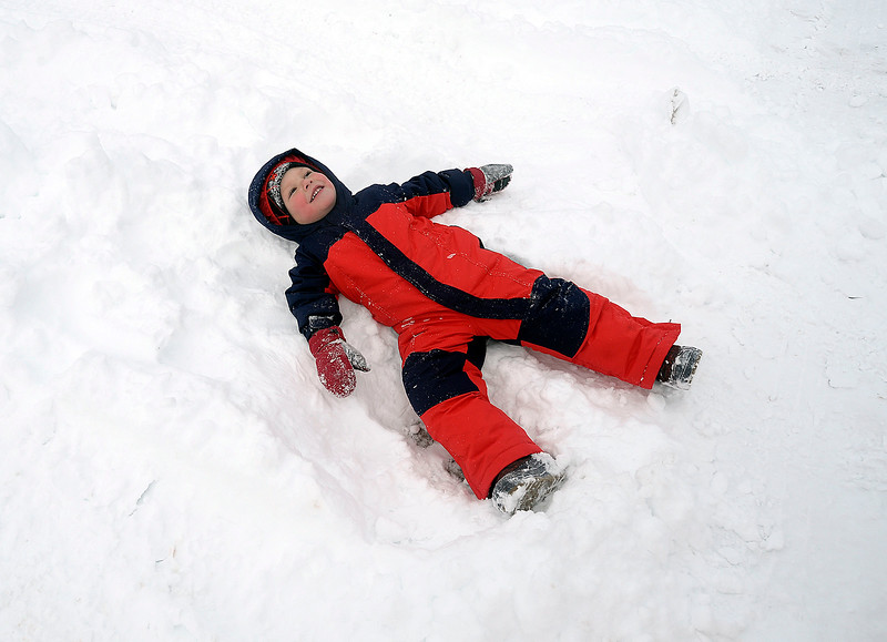 William Veigel, 3, lays down in the snow as his family shovels snow Thursday, Jan. 5, 2017, on the 1900 block of Estrella Avenue in west Loveland. (Photo by Jenny Sparks/Loveland Reporter-Herald)