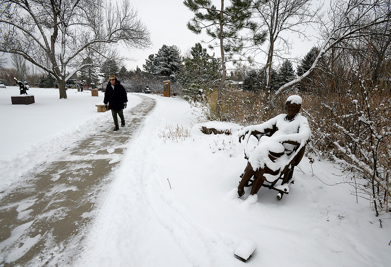 Laurie Paulik of Loveland walks in the snow at Benson Park Sculpture Garden on Wednesday, Dec. 7, 2016, in northwest Loveland. (Photo by Jenny Sparks/Loveland Reporter-Herald)