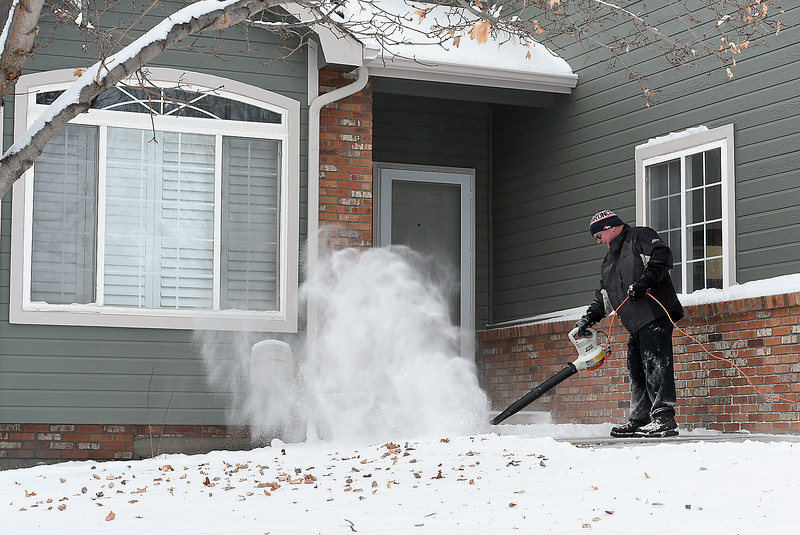 "Barry Atkinson uses a leaf blower to clera snow from his porch Wednesday, Dec. 7, 2016, on the 3800 block of Drake Ct. in northwest Loveland. ""It was bound to come sooner or later,"" he said while clearing snow. (Photo by Jenny Sparks/Loveland Reporter-Herald)"