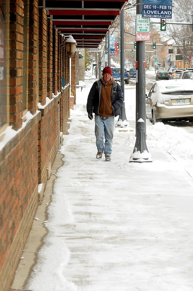 Loveland resident John Grimes walks down the snowy sidewalk on Lincoln Avenue between Fifth and Fourth streets in downtown Loveland on Wednesday morning, Dec. 7, 2016. Grimes said he was wearing about six layers of clothing against the 9-degree cold. (Photo by Craig Young / Loveland Reporter-Herald)