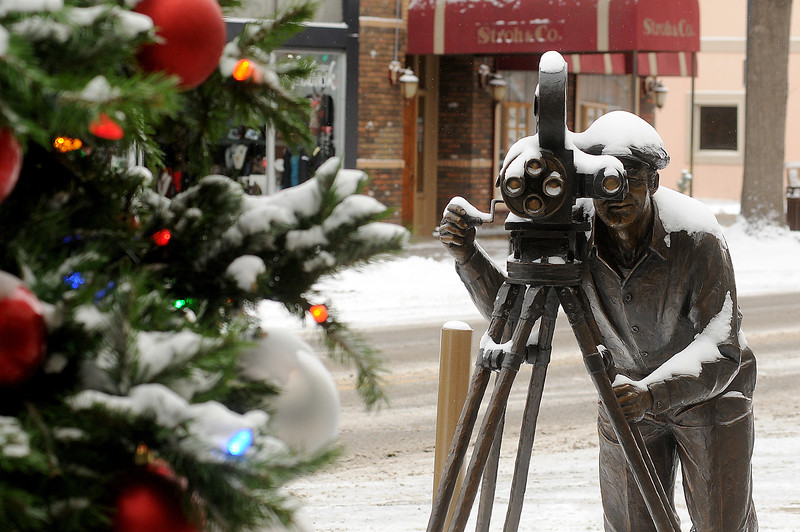 "A snow-covered bronze cameraman seems to be filming the Christmas tree in front of the Rialto Theater in downtown Loveland on Wednesday morning, Dec. 7, 2016. The city received about 3 1/2 inches of snow overnight, and temperatures dipped to 9 degrees below zero. The sculpture, ""Persistence of  Vision"" by Pat Kennedy, was placed outside the historic movie theater in honor of the late Phyllis Walbye, longtime arts and entertainment editor at the Reporter-Herald. (Photo by Craig Young / Loveland Reporter-Herald)"