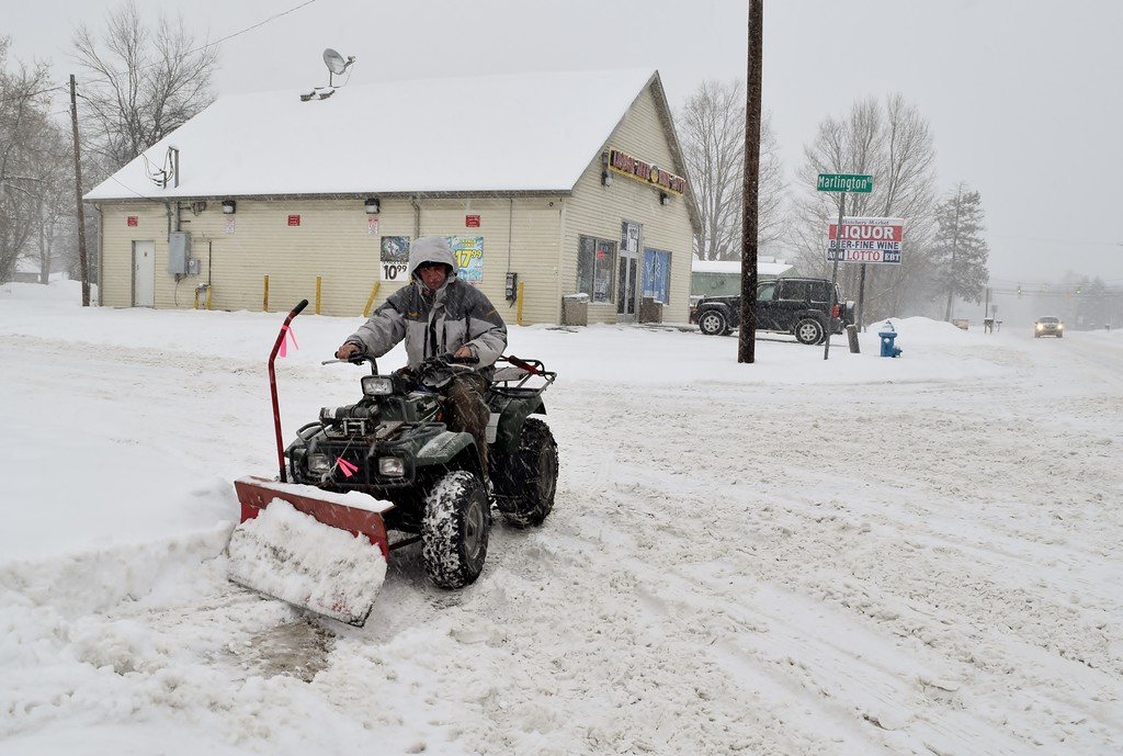 . Clearing the snow off near Waterford Kettering High School. Photo by Natalie Broda / The Oakland Press.