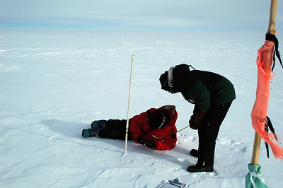 "SOUTH POLE STATION, ANTARCTICA: The ""snow stakes"" are just PVC pipe that was planted vertically when the project started in 1990. Since then, the drifting snow has pushed the stake over somewhat while burying it in the drift snow. A red and green flagged bamboo helps us find a white stake in a white landscape."