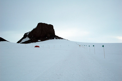 CASTLE ROCK, ROSS ISLAND, ANTARCTICA: Getting closer, we approach another warming hut, this one slightly larger at the base of Castle Rock.