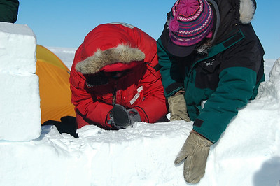 SOUTH POLE, ANTARCTICA: Kari holds a newly places block steady as Chris makes final adjustments fitting it right into place.
