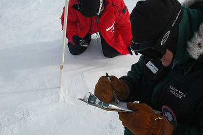 SOUTH POLE STATION, ANTARCTICA: Randi reads off the angle measurement and Kris records both the short and long length of the pole if an extension was added. Otherwise we just record how long the pole is and compare that to last year's measurement.