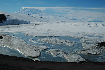 MCMURDO STATION, ANTARCTICA: Late in the summer like this, the thinner sea ice starts to break up, especially along the shore where the dark ground is easily warmed by the constant sunshine. Erebus in the background.