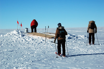 SOUTH POLE STATION, ANTARCTICA: Finally, we arrive at the pit where the hole down to the buried aircraft has been started. Chris looks down to investigate while Kari and Mike get their skis off.