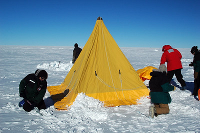 SOUTH POLE, ANTARCTICA: Arik and Phil shovel snow on the base flaps of the Scott Tent to help hold it down and to keep wind and snow from drifting underneath and into the floorless shelter.