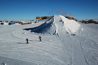 SOUTH POLE STATION, ANTARCTICA: Looking down from atop a similar, yet smaller snow mound as seen here, two of our intrepid ski explorers ski past the sledding hill toward the skiway in search of buried aircraft.
