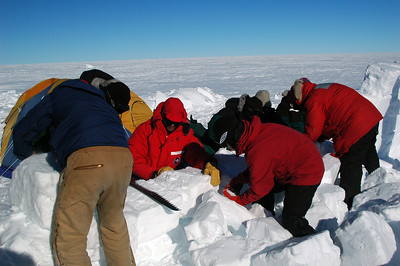 SOUTH POLE, ANTARCTICA: After putting the Scott Tent up we turn our team on a fallen snow wall. We get it rebuilt to act as a windbreak to protect camp.