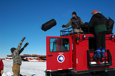 """SOUTH POLE, ANTARCTICA: Antarctic Car Camping: John tosses Pete and Arik a sleeping bag to pack on the top of our """"car"""" to head out in to the great white nothing to go camping for the night."""