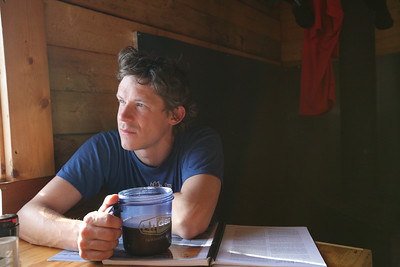 WHITE MOUNTAINS, AK - Wolf Run Cabin. Nathaniel pauses to think amidst his reading on the first of our two rest days.