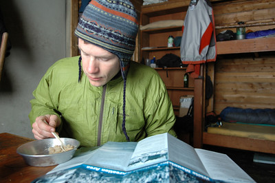 WHITE MOUNTAINS, ALASKA. Moose Creek Cabin. Nathaniel eats oatmeal and checks out the informational map (not to be used for navigation).