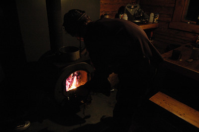 WHITE MOUNTAINS, ALASKA. Moose Creek Cabin - stoking the fire.