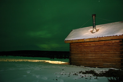 WHITE MOUNTAINS, ALASKA. Moose Creek Cabin - Northern lights turning the cloud cover green with a little head lamp painting on the back of the cabin.