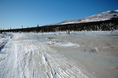 WHITE MOUNTAINS, ALASKA. Icy overflow water frozen along the trail. Caused by the compacting of the snow along the trail not letting ground water and meltoff flow past the trail.