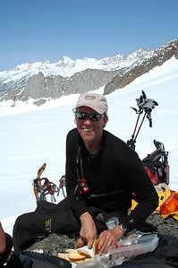 Daniel carves up some lunch on the frozen shore of Glacier Lake with the well known Whaleback ridge in the near background, and the continuance of the Great Western Divide to the north in the distance.