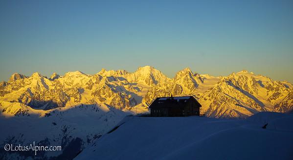 Sunrise illuminates the French Alps behind the Cabane du Mont Fort....Verbier, Switzerland