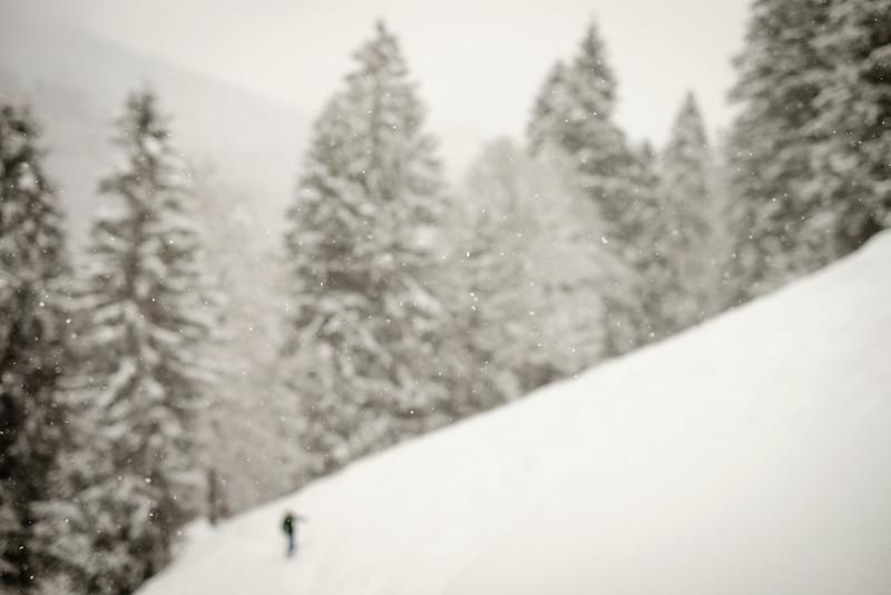 Ski tourer climbing with snow falling in the Wägital, Swiss alps