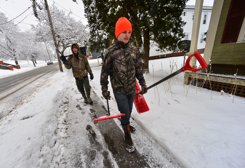 KRISTOPHER RADDER — BRATTLEBORO REFORMER<br /> Harrison Gleim, 16, and Jordan Keefe, 16, of Bellows Falls, walk around the community with shovels in their hands to clear out driveways for local residents after a snowstorm on Thursday, Feb. 13, 2020.