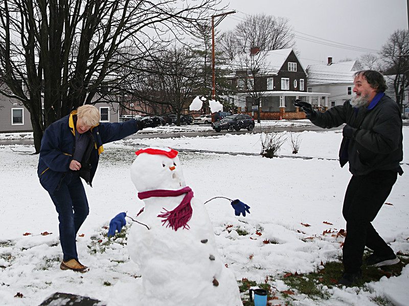HOLLY PELCZYNSKI - BENNINGTON BANNER Ruth Farmsworth and Jay Dodge of Bennington enjoy a fun snowball fight while building a snowman on Tuesday afternoon in Bennington.