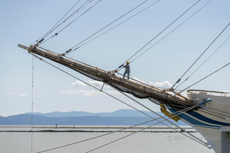 Japanese crewman on the bow sprit of Kaiwo Maru adjusting a forestay, Steveston, British Columbia