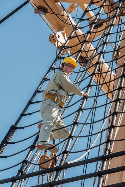 Smiling crewman on the mizzen mast ratlines, Kaiwo Maru, Stevenston pier, British Columbia