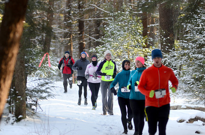 Participants in the CJ's Resolution Challenge run at R.B. Winter State Park on Saturday make their way along a snowy course despite the cold weather.