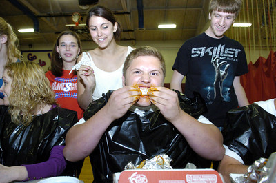Harley Stahl, 17, center, chows down a chicken wing as counters Tara Benner, 18, second from left, and Andrew Swineford, 18, right, watch on at the Selinsgrove High School on Thursday.