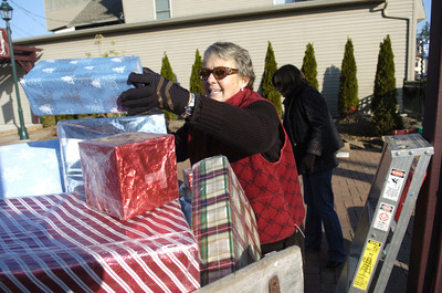 Janie Shoner of Selinsgrove puts presents on a sled in the Selinsgrove Commons on Monday as part of a decorating effort for the downtown.