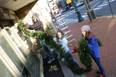 Selinsgrove High School students Nick Ney, 17, left, Ellen Spriggle, 17, and Gabby Singh, 17, hang up some greens to help decorate the Selinsgrove downtown on Monday morning.
