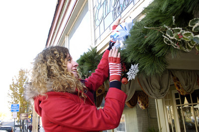 Courtney Conrad, 18, attaches a bow to some holiday decorations in downtown Selinsgrove on Monday as the borough gets ready for the holiday seasons.