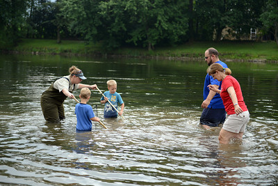 Amanda August/For The Daily Item Shannon Burkland-Stamm, a water specialist for the Union County Conservation District, helps Graham, 5, and Jay Yount, 6 of Middleburg, hold up a net while Jason Winey and Janet Bilger walk towards them to collect insect and fish specimens during the Ecology and Outreach Program held by the Lower Penns Creek Watershed Association in New Berlin on Saturday morning.