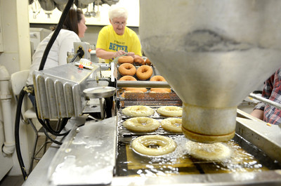 Bernie Schwalm, left, Middleburg, and Kate Saylor, Beavertown, collect donuts at the end of the conveyor on Monday at the Beavertown Rescue Hose Company as they prepare for donut day, today.