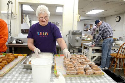 Martha Aumiller of Beavertown coats donuts in sugar as she helps out at the Beavertown Rescue Hose Company on Monday as they prepared for donut day today.