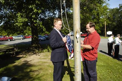State Representative Fred Keller, left, and Tony Korzenaski, raise the American flag during a flag ceremony on Thursday morning outside the career link in Selinsgrove.