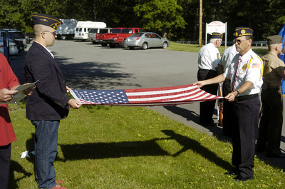 Vincent Stoops, Second Vice Commander, left, and Honor Guard Commander Ron Cowan of Selinsgrove, right, participates in a Flag Day ceremony on Thursday outside the Career Link in Selinsgrove.